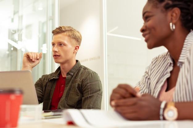 Kurs językowy. uważny blond młody mężczyzna jest we wszystkich uszach podczas lekcji