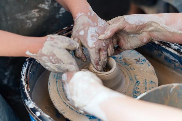 Kurs mistrzowski na temat nauczania ceramiki. ręce tworzą glinianą figurkę.