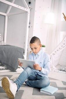 Kurs online. przyjemny chłopiec afroamerykański uczący się podczas korzystania z tabletu