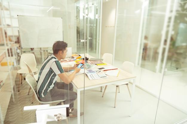 Kurs online. uważny azjatycki mężczyzna czytający wiadomość i siedzący sam w klasie