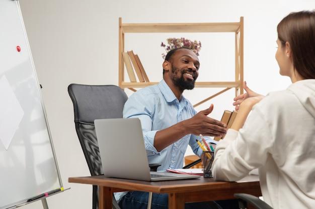 Kursy języka angielskiego w domu. uśmiechnięty mężczyzna uczy studenta we wnętrzu salonu