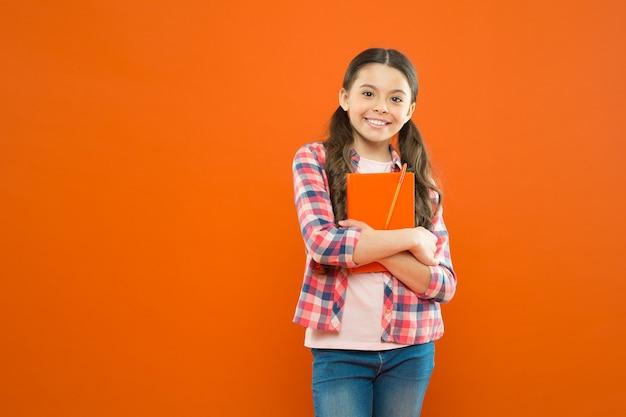 Kursy online dla dzieci. dziewczyna dziecko przytulić podręcznik pomarańczowe tło. nauka jest fajna. dodatkowy kurs szkolny. koncepcja szkoły. uczeń prowadzenia podręcznika. kursy językowe dla młodzieży. kursy edukacyjne.
