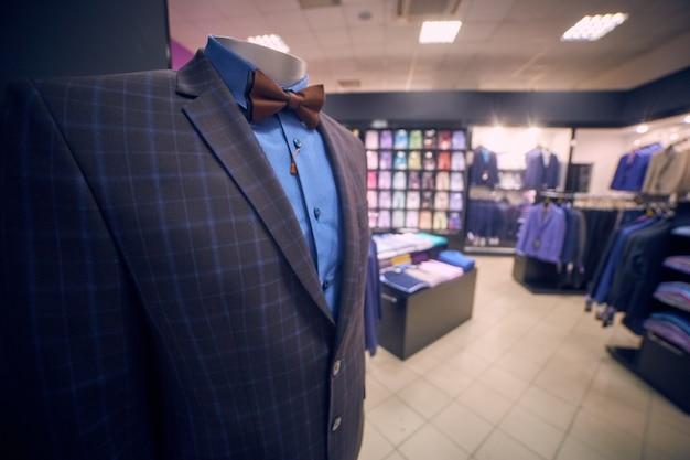 Kurtka, koszula, motyl na manekinie w butiku z męską odzieżą