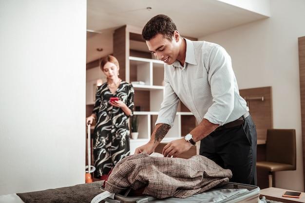 Kurtka w walizce. przystojny mąż z tatuażem na dłoni wkłada swoją kraciastą kurtkę do walizki