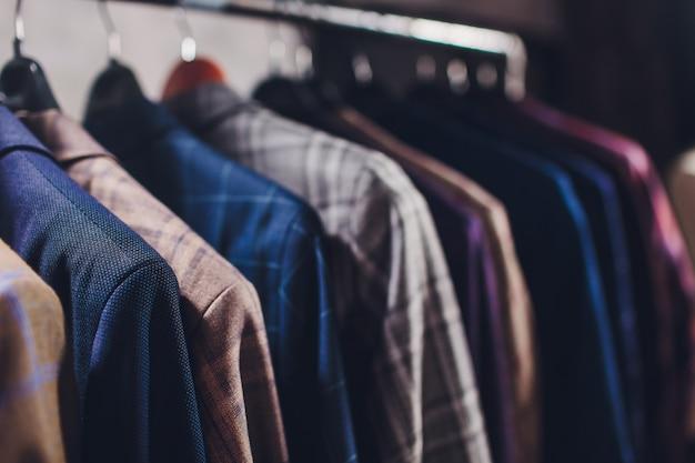 Kurtki obrabiane na wieszaku na ubrania w pracowni krawieckiej.