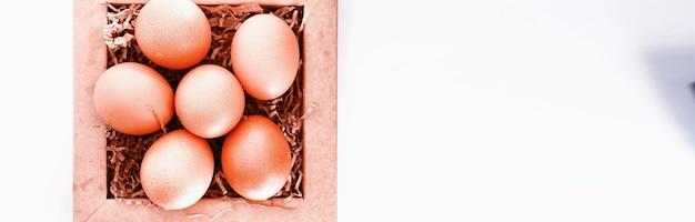 Kurze brązowe jajka na białym stole w małym koszyczku