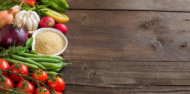 Kuskus w misce i świeże warzywa na brązowy drewniany stół z bliska