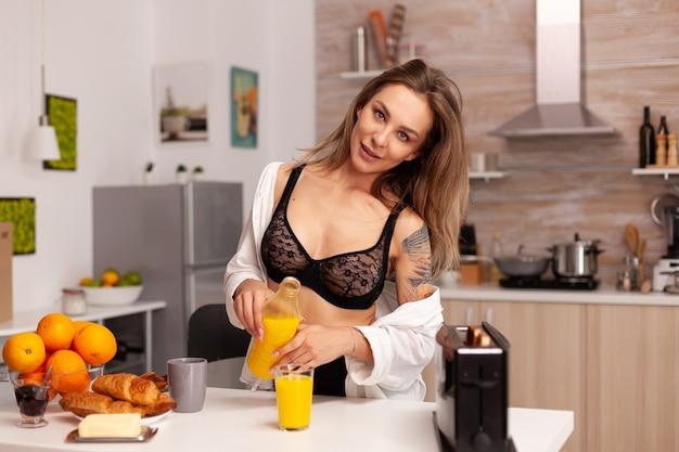 Kusząca kobieta przygotowuje pyszne i zdrowe śniadanie na sobie seksowną czarną bieliznę. młoda seksowna uwodzicielska dama z tatuażami pijąca zdrowy, naturalny domowy sok pomarańczowy