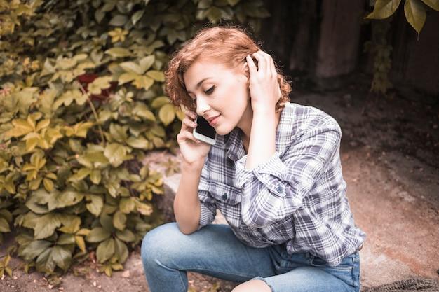 Kusząca kobieta z urządzeniem przy ulicy z krzewami