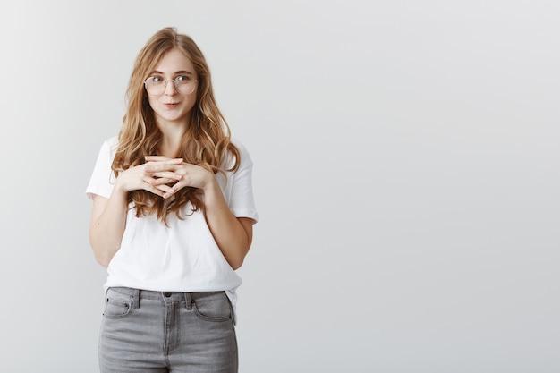 Kusząca ładna blond dziewczyna uśmiecha się i patrzy w lewo z pożądaniem i zachwytem
