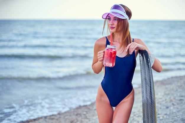 Kusząca nowoczesna brunetka w niebieskim stroju kąpielowym i różowej czapce stojącej z deską na plaży.