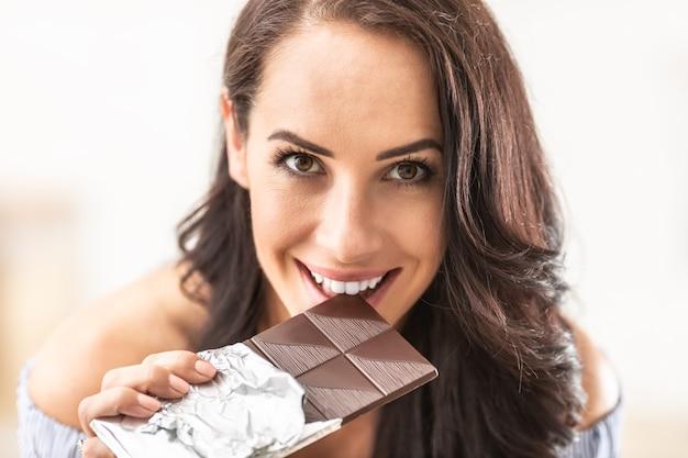 Kusząco wyglądająca kobieta odgryza tabliczkę czekolady, uśmiechając się.