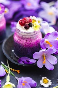 Kusząco wyglądający słoiczek fioletowego wegańskiego smoothie z jagodami, otoczony wiosennymi kwiatami