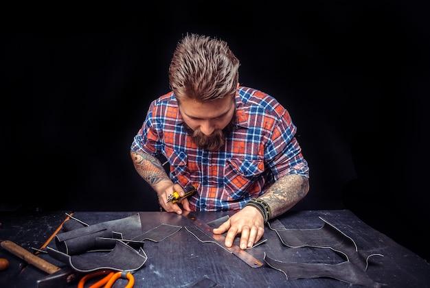 Kuter skórzany pracujący przy galanterii skórzanej w swoim miejscu pracy