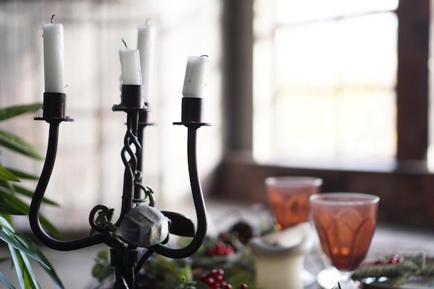 Kuty metalowy świecznik ze świecami na rozmytym tle ze światłem z okna