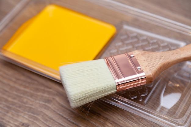 Kuweta malarza zbliżenie z żółtą farbą na drewnianej brązowej podłodze, naturalny pędzel. widok z góry. kolorowe jasne kreatywne wnętrze dla młodej rodziny. jak malować drewnianą powierzchnię