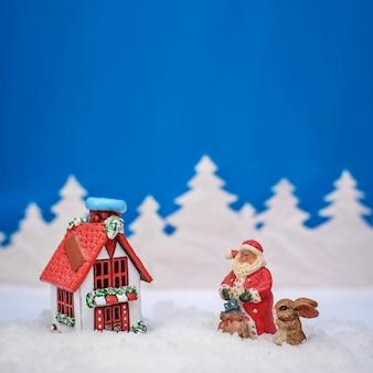 Kwadratowa niebieska kartka świąteczna, na której święty mikołaj i zajączek są na zewnątrz domu z czerwonym dachem w pobliżu pokrytego śniegiem lasu