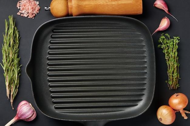 Kwadratowa pusta patelnia na tle czarnego stołu z przyprawami i przyprawami. przybory grillowe do grillowania mięsa lub warzyw. widok z góry z miejsca kopiowania tekstu.