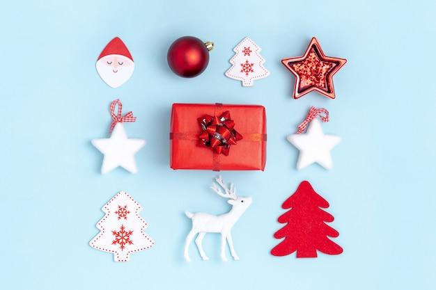 Kwadratowa ramka z czerwonymi kulkami, białymi gwiazdami, choinką, jeleniem i pudełkiem na pastelowym niebieskim papierze