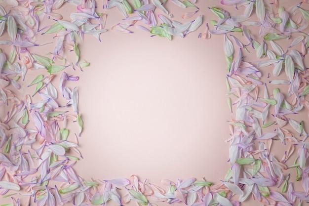 Kwadratowa ramka z płatkami kwiatów w niebiesko-fioletowych odcieniach fioletu, na jasnoróżowym kremowym tle.