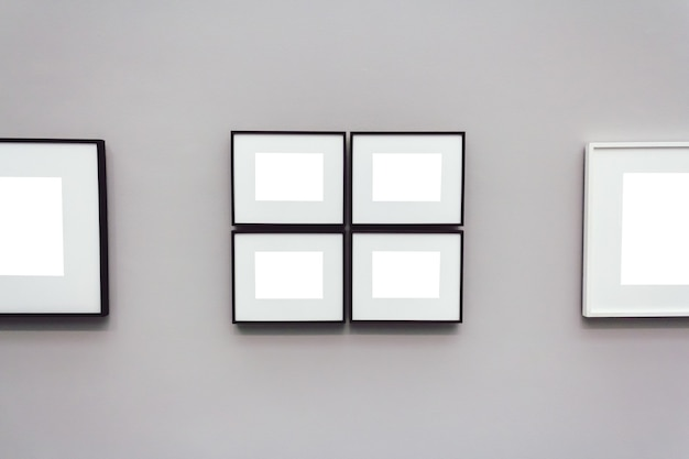 Kwadratowe białe puste ramki przymocowane do szarej ściany