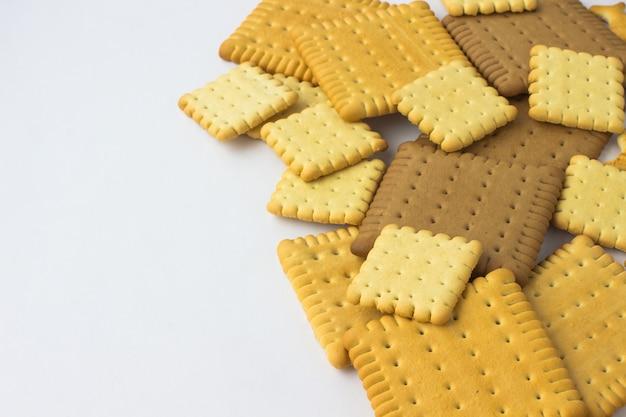 Kwadratowe ciasteczka na białym stole.