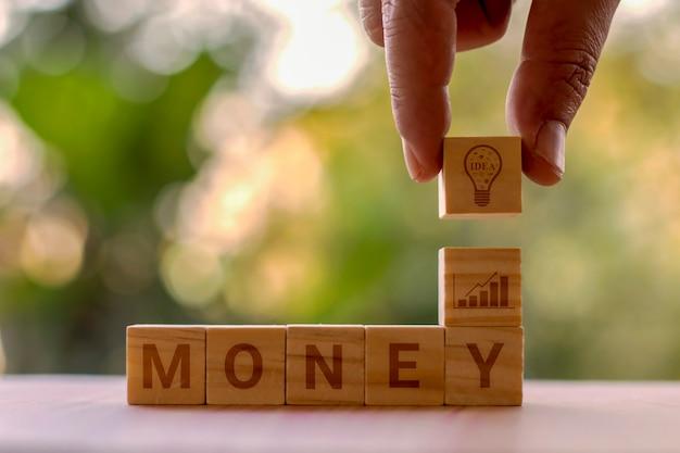 Kwadratowe drewniane klocki z banknotami i pomysłami na planowanie zakupów oraz pomysłowość zakupów.