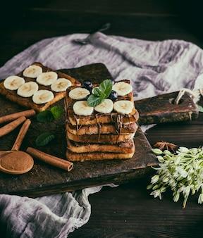Kwadratowe francuskie tosty z białego chleba z czekoladą i kawałkami banana