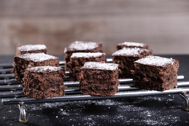 Kwadratowe kawałki czekolady i ciasta ze szkła cukrowego na stalowej siatce