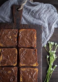 Kwadratowe kawałki smażonego białego chleba rozmazane czekoladą