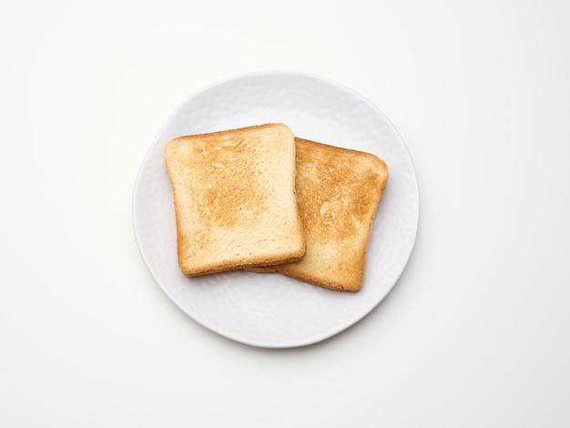Kwadratowe kawałki tostowego chleba z białej mąki pszennej na okrągłym talerzu. białe tło stołu