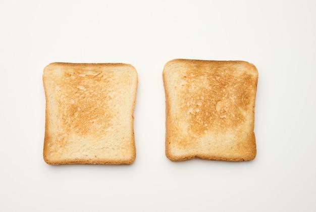Kwadratowe kromki chleba z białej mąki pszennej opiekane w tosterze, widok z góry