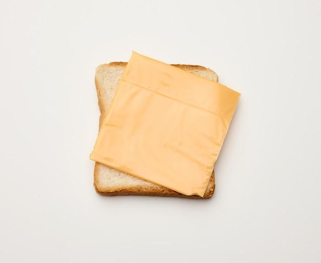 Kwadratowe kromki tostowego chleba z białej mąki pszennej i plasterka sera cheddar na wierzchu. białe tło stołu