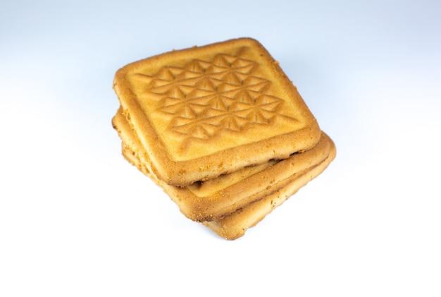 Kwadratowe kruche ciasteczka na białym tle z ornamentem na nim. stos ciasteczek, zdjęcie ciepłego domowego jedzenia, układ na instagramie. czworokątne pliki cookie.