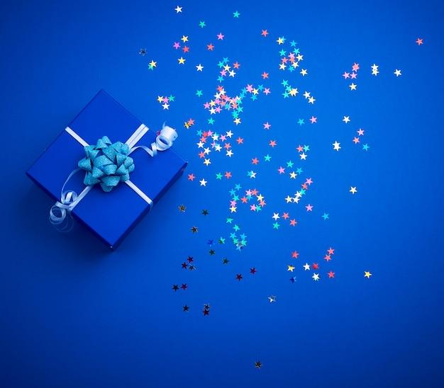 Kwadratowe lśniące niebieskie pudełko z kokardą i wielobarwne iskierki na niebieskim