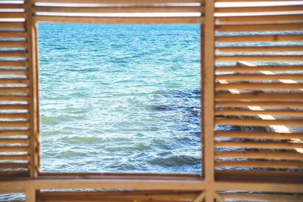 Kwadratowe okno z widokiem na błękitne morze i błękitne niebo.