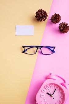 Kwadratowe okulary na różowym i żółtym tle z dodatkowymi dodatkami, budzikiem i kwiatami sosny. minimalistyczny letni styl
