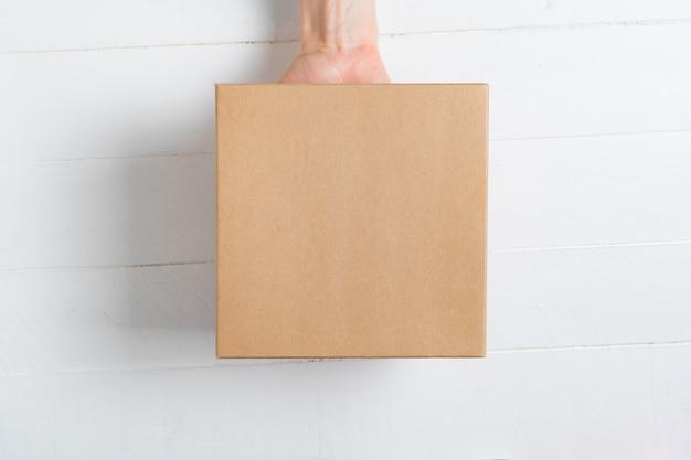 Kwadratowe pudełko kartonowe w kobiecej dłoni.