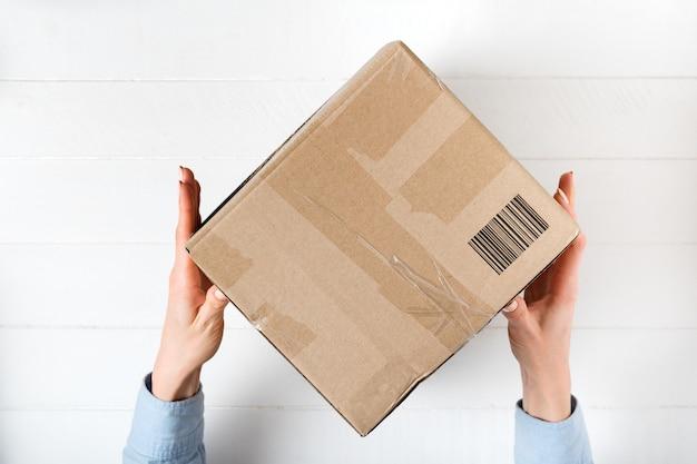 Kwadratowe pudełko kartonowe z kodem kreskowym w rękach kobiet.