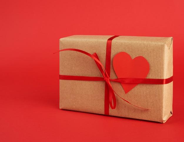 Kwadratowe pudełko owinięte prezentem z brązowego papieru rzemieślniczego i przewiązane cienką jedwabną czerwoną wstążką