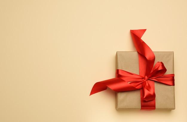 Kwadratowe pudełko zapakowane w czerwony papier i zwiniętą jedwabną tasiemkę, świąteczne tło, widok z góry
