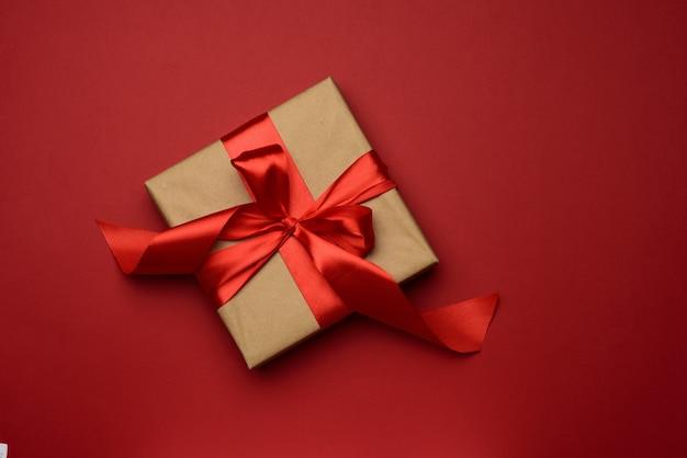 Kwadratowe pudełko zapakowane w czerwony papier i zwiniętą jedwabną wstążkę na czerwonym tle, tło świąteczne, widok z góry