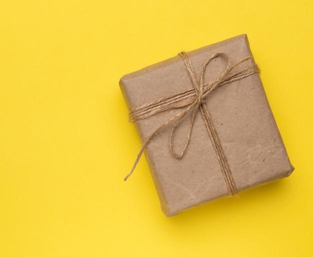 Kwadratowe pudełko zawinięte w brązowy papier i przewiązane brązową liną