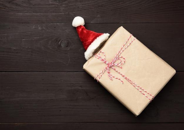 Kwadratowe pudełko zawinięte w brązowy papier pakowy i czerwoną czapkę, prezent na drewnianym, widok z góry