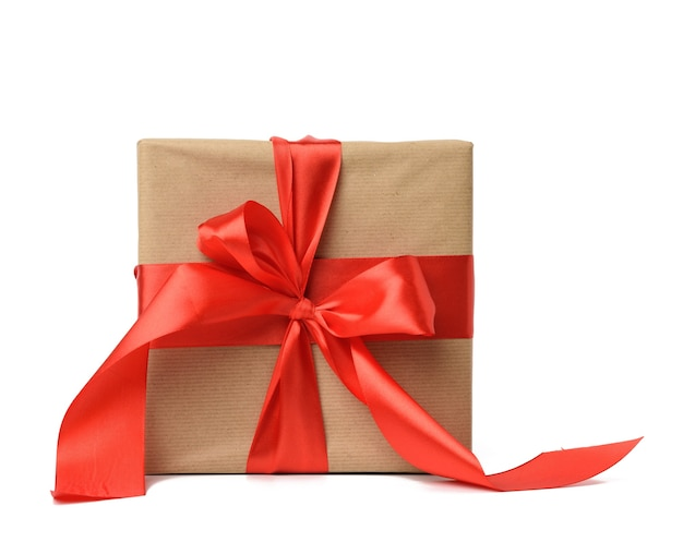 Kwadratowe pudełko zawinięte w brązowy papier pakowy i przewiązane czerwoną jedwabną wstążką, białe tło