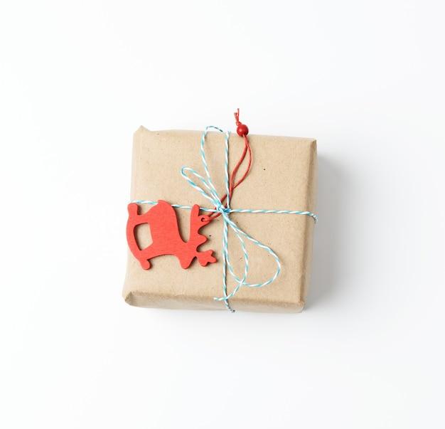 Kwadratowe pudełko zawinięte w brązowy papier pakowy i przewiązane czerwoną liną, prezent na białym tle