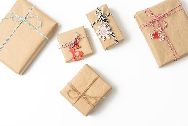 Kwadratowe pudełko zawinięte w brązowy papier pakowy i przewiązane liną, prezent na białej powierzchni, widok z góry