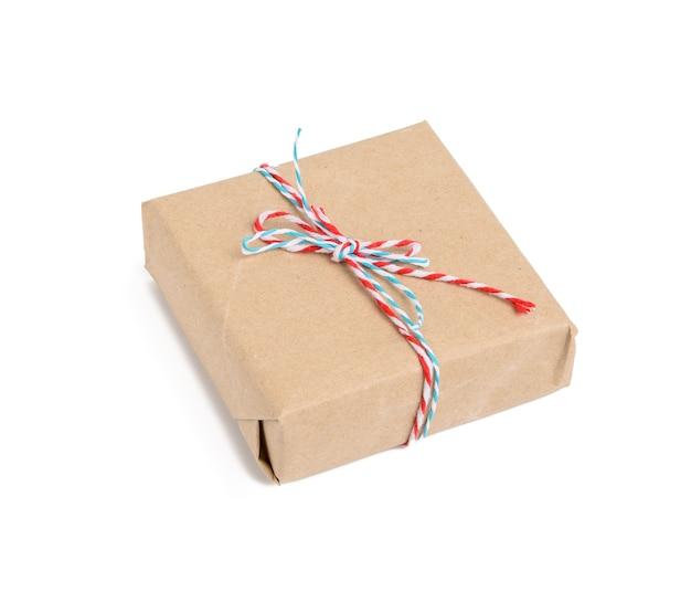 Kwadratowe pudełko zawinięte w brązowy papier pakowy i związane czerwoną liną, prezent na białym tle