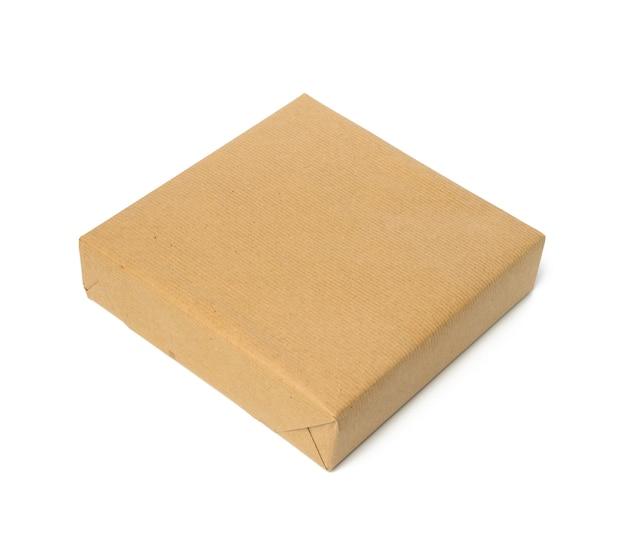 Kwadratowe pudełko zawinięte w brązowy papier pakowy, opakowanie na białym tle