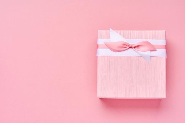 Kwadratowe różowe pudełko z czerwoną wstążką na różowym tle. pocztówka koncepcja walentynki. widok z góry.
